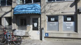 Image of accessible library entrance with blue awning and access pad